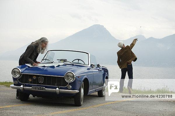 Seniorenpaar mit Cabrio am Meer  Italien  Gardasee Ostufer