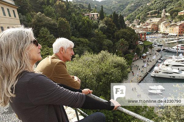 Seniorenpaar schaut auf Hafen und Häuser  Italien  Portofino