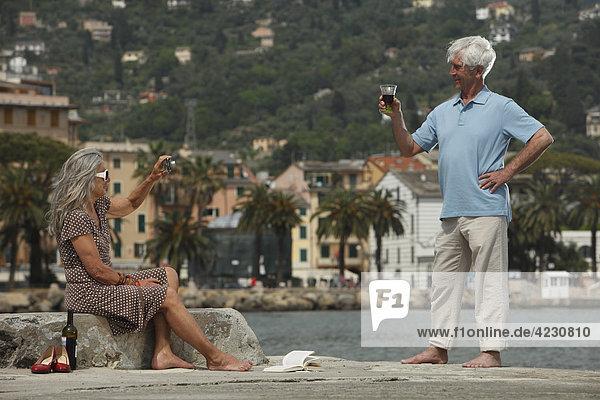 Seniorenpaar trinkt Rotwein am Wasser  Italien  Rapallo