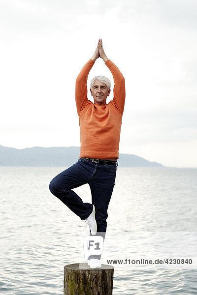 Senior macht eine Yogaübung am Wasser  Italien  Gargnano  Gardasee
