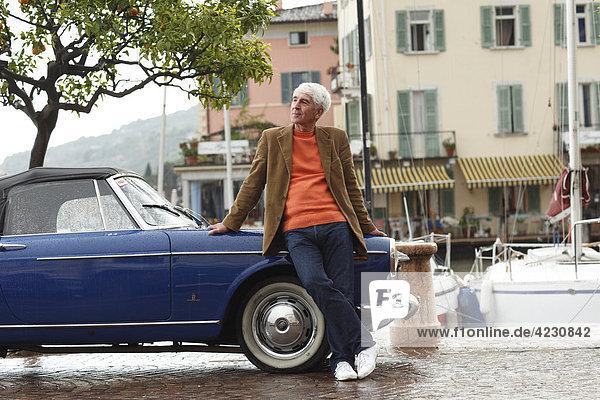 Senior lehnt an Oldtimer am Hafen  Italien  Gargnano  Gardasee