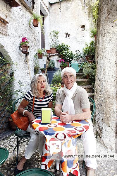 Seniorenpaar sitzt an Tisch im Freien  Italien  Malcesine