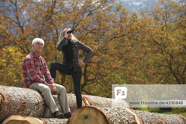 Seniorenpaar mit Fernglas auf Baumstämmen  Italien  Telve  Dolomiten