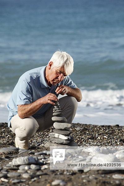Senior stapelt Steine am Strand  Italien  Sori