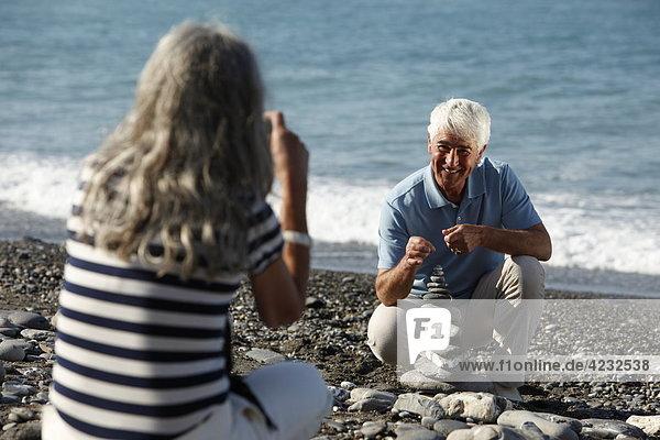 Seniorin fotografiert Mann am Strand  Italien  Sori