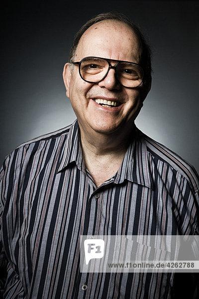 Studio-Porträt des fröhlichen Senior-Mannes