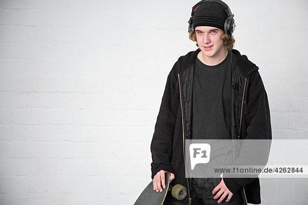 Portrait of teenage boy with skateboard