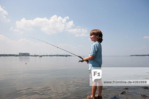 Kleiner Junge beim Fischen am Strand