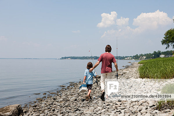 Father and son walking along beach with fishing rods