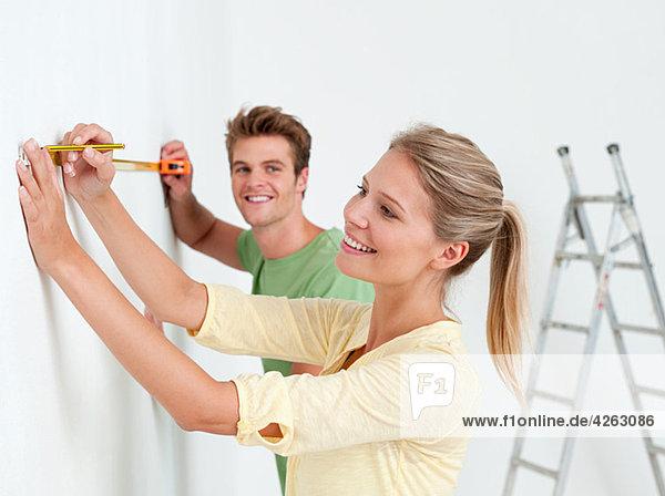 Junges Paar mit Maßband an der Wand