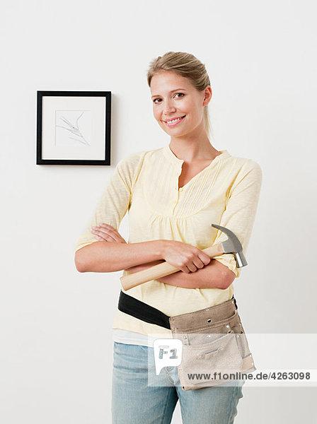 Junge Frau mit Hammer und Bild an der Wand