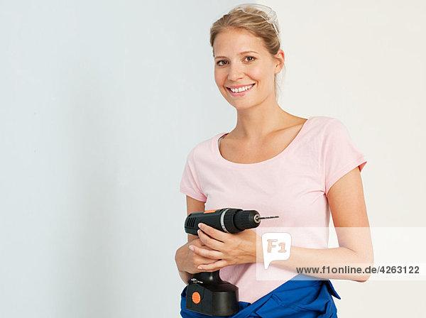 Junge Frau mit einer elektrischen Bohrmaschine