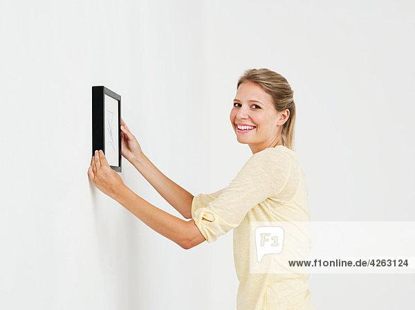Junge Frau hängt Bild an der Wand