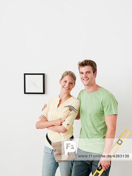 Junges Paar mit Werkzeugbild an der Wand