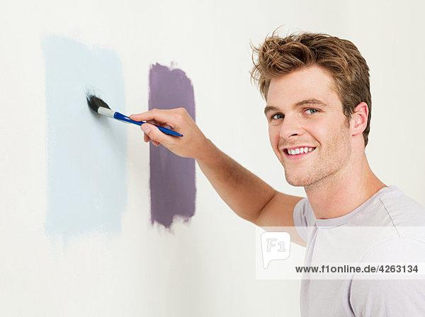 Junger Mann beim Malen einer Wand