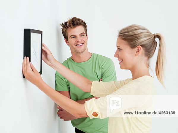 Junges Paar beim Aufhängen eines Bildes