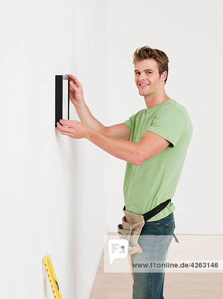 Junger Mann hängt Bild an der Wand