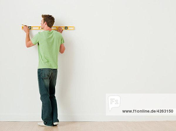 Junger Mann mit Wasserwaage an der Wand