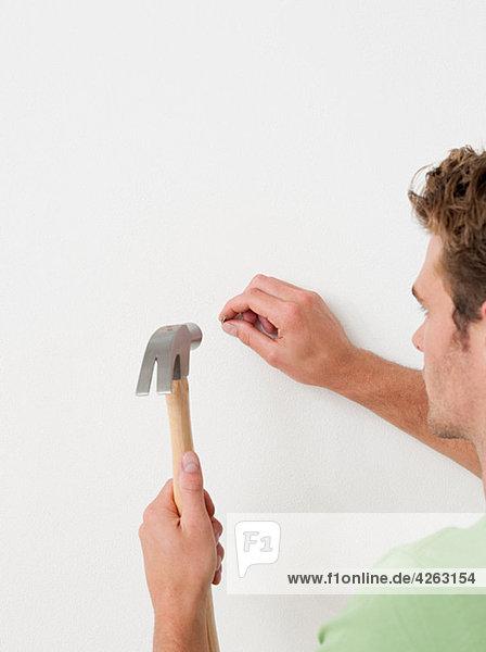 Junger Mann schlägt Nagel in die Wand
