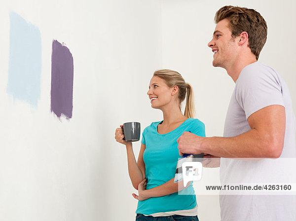 Junges Paar schaut auf Farbe an der Wand