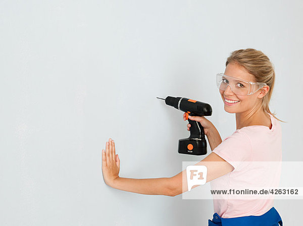 Junge Frau mit Elektrobohrer