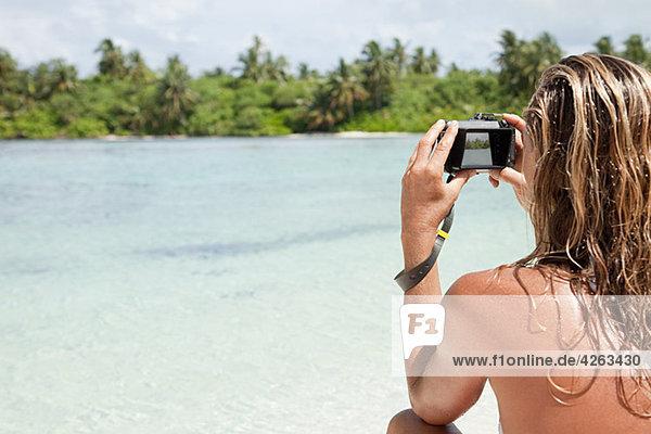 Woman taking picture  Medahutthaa Island  North Huvadhu Atoll  Maldives