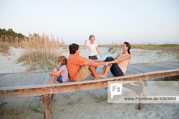 Familie sitzt zusammen auf einem Strandsteg