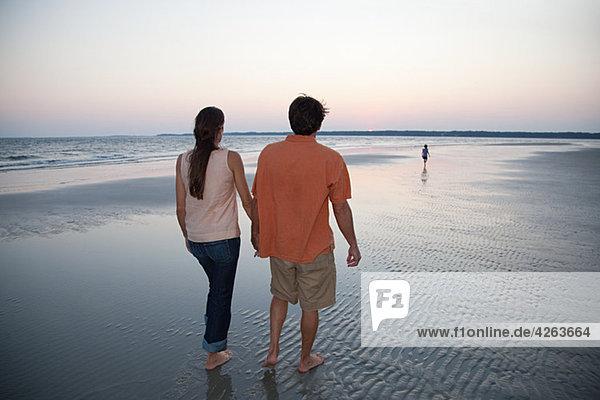 Paar Wandern am Strand mit Tochter in Entfernung