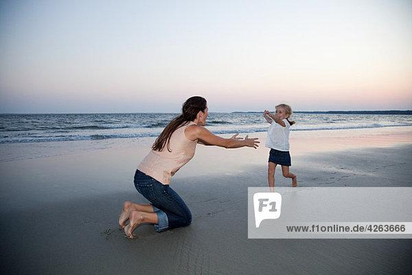 Mädchen rennt zur Mutter am Strand