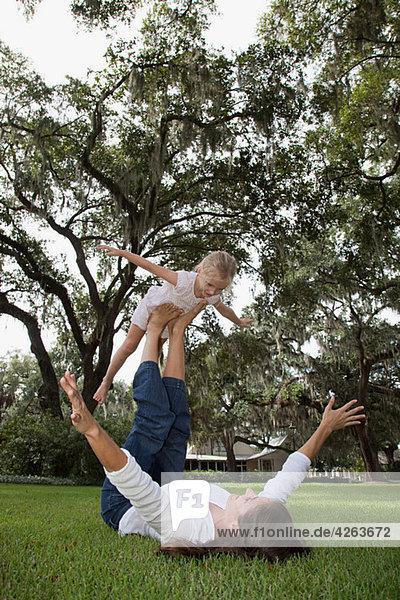 Mädchen balanciert auf den Füßen der Mutter