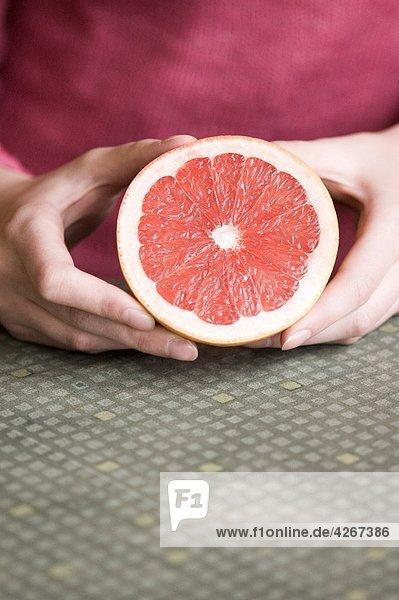 junge Frau mit Hälfte der grapefruit junge Frau mit Hälfte der grapefruit