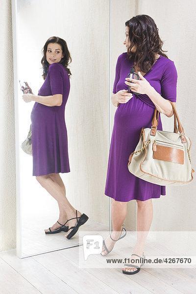 Pregnant Frau blickt auf Spiegel