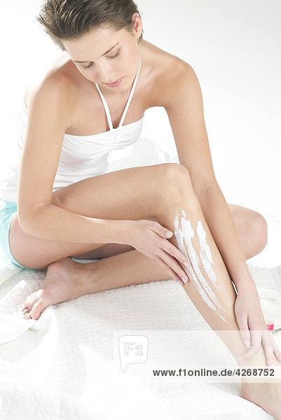 junge Frau  Lotion auf Beine