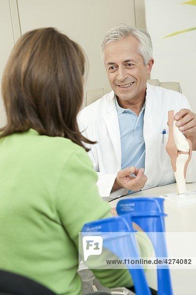 Arzt zeigt einer Patientin ein künstliches Kniegelenk