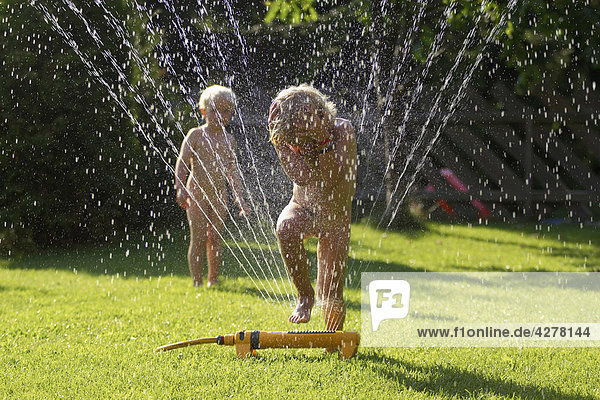 kinder spielen mit sprinkler in garten beyond fotomedia. Black Bedroom Furniture Sets. Home Design Ideas