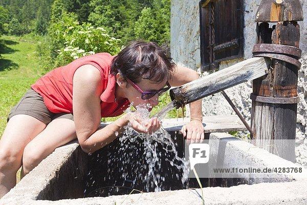 Frau trinkt Wasser vom Brunnen  Hallstatt  Salzkammergut  Österreich  Europa