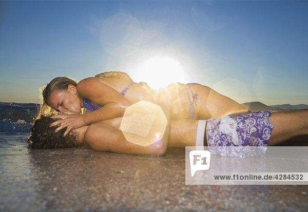 Sexy cple. Kuss bei Flut am Strand