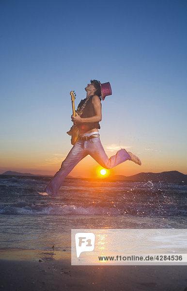 Junger Mann springt mit Gitarre bei Sonnenuntergang