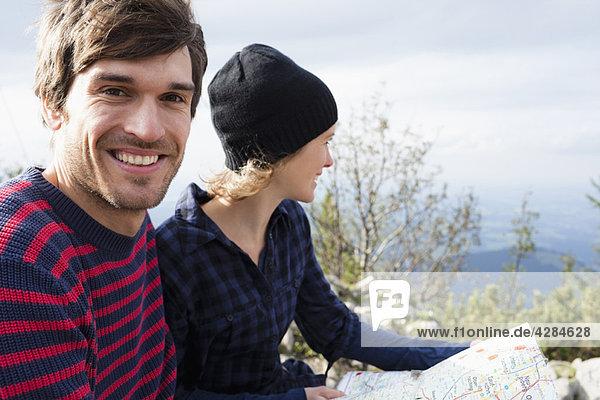 Paar mit Karte vor der Landschaft