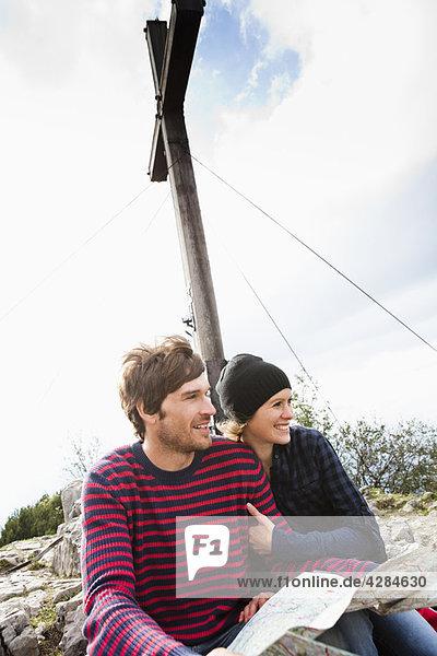 Paar mit Karte unter dem Kreuz sitzend