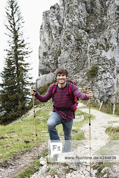 Mann mit Wanderstöcken auf dem Bergweg