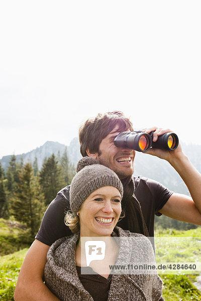 Paar mit Fernglas zur Beobachtung der Landschaft