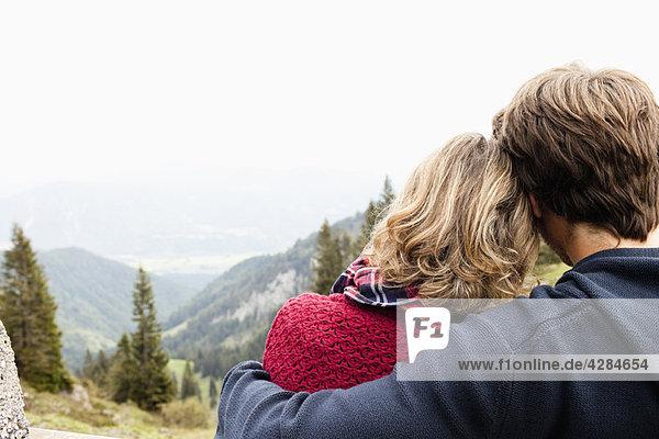 Mann umarmt Frau beobachtet Landschaft