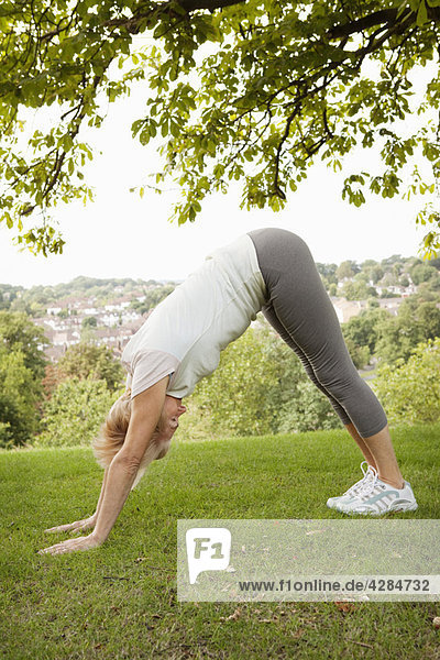 Reife Frau beim Yoga-Stretch im Park
