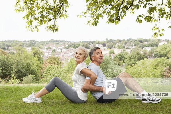 Erwachsenes Paar  das sich Rücken an Rücken streckt
