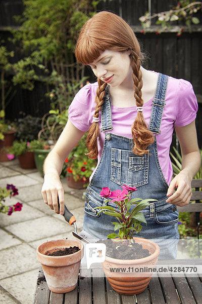 Frau Umtopfpflanze im Garten