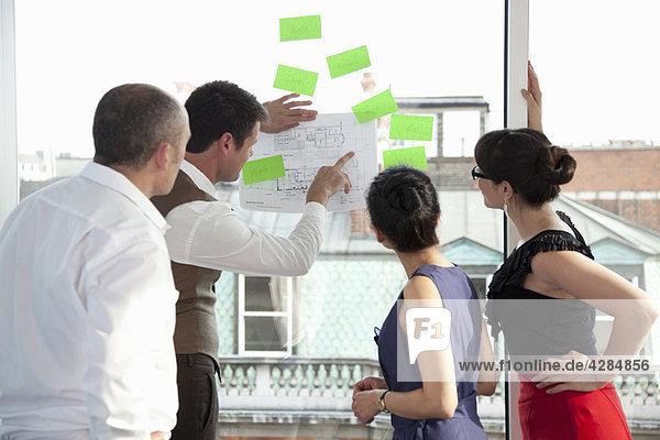Arbeitskollegen schauen sich Pläne an