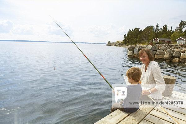 Lächelnde Großmutter beobachtet Fischerjunge