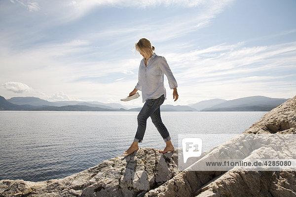 Frau beim Spaziergang am felsigen Strand am Meer