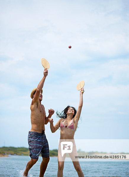 Paar spielt Beachball am Strand
